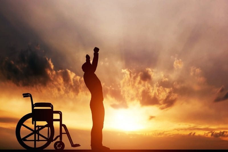 Man Standing From Wheel Chair With Arms In The Air